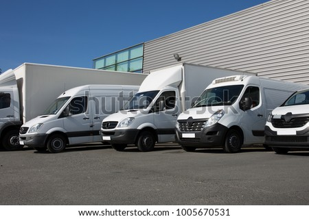 White Delivery Trucks Backed Up to A Warehouse Building #1005670531