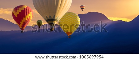 Cappadocia at sunrise - many colorful hot air balloons flight above mountains. Panoramic landscape with blue silhouettes of mountains and balloons for your concept of travel, adventures or dreams. #1005697954