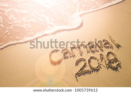 Message for Carnaval 2018 written on smooth sand beach as wave washes up in Rio de Janeiro, Brazil