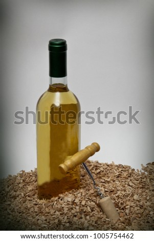 Corkscrew with a cork and a glass bottle of wine on a wood chips background #1005754462