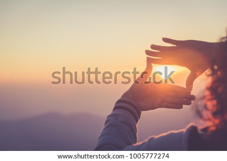 The woman making frame round the sun with her hands in sunrise,copy space,warm retro tone. #1005777274