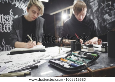 Portrait of the masters of calligraphy. Tattoo artists make a sketch sitting at the table in the Studio. This working process #1005816583