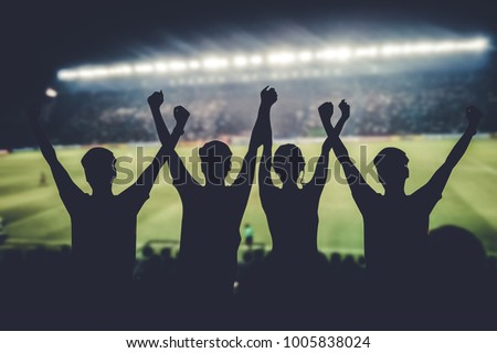 silhouettes of Soccer fans in a match and Spectators at football stadium #1005838024
