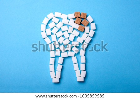 Sugar destroys the tooth enamel and leads to tooth decay. Sugar cubes are laid out in the form of a tooth and brown sugar symbolizes caries. #1005859585