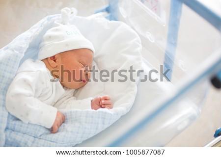 Beautiful newborn baby boy, laying in crib in prenatal hospital Royalty-Free Stock Photo #1005877087