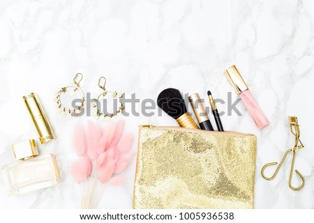 ?osmetics for makeup gold with pink. Flat lay