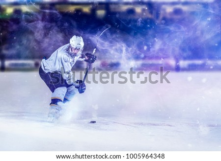 ice hockey player in action kicking with stick #1005964348