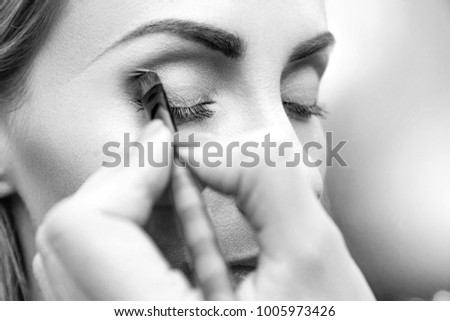 Makeup artist doing eyemakeup with brush. Eyeshadow in the corner of the eyelid. Closeup side view. Black and white photo. Unfocused background. #1005973426
