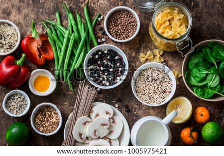 Flat lay vegetarian healthy food set - grains, vegetables, fruit, pasta, seeds on a brown wooden background, top view. Healthy food concept  #1005975421