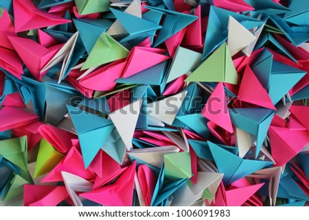 Colorfull origami 3d units isolated on white with shadow. From sheets of paper making modules. Modular origami - green, white, red, light-blue, triangle modules. Abstract background. #1006091983