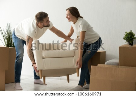 Young couple carrying chair together, house improvement, modern furniture in new home concept, man and woman moving into own flat after relocation furnishing living room, remodeling and renovation #1006160971