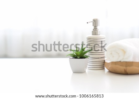 Ceramic soap, shampoo bottles and white cotton towels on white counter table inside a bright bathroom background. #1006165813