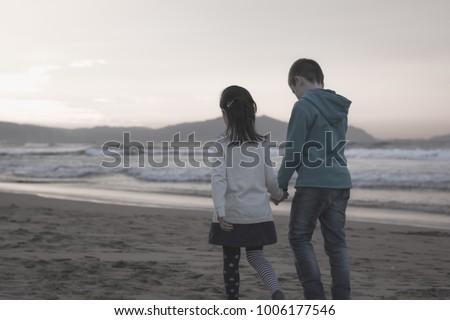 Couple of children walk together in winter season on empty Arrietara beach, north Spain. Innocent romantic scene of kids holding hands at sunset, Valentine's day love concept #1006177546