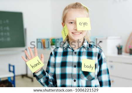 Happy schoolgirl having sticky notepapers with English names of body parts on her hand, cheek and eye Royalty-Free Stock Photo #1006221529