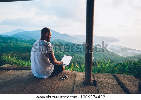 Rear view of male traveler blogger work remote on netbook computer while enjoying amazon nature landscape view outdoors. Young man using online banking for sending money everywhere you are from laptop Royalty-Free Stock Photo #1006574452