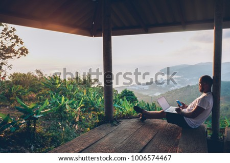 Young man traveler using laptop computer while enjoying beautiful tropical sunset in Thailand. Freelancer guy working on freelance on netbook during vacation holidays in summer. Male adventure blogger Royalty-Free Stock Photo #1006574467
