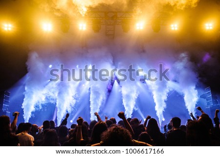 Picture of rock concert, music festival, New Year eve celebration, party in nightclub, dance floor, disco club, many people standing with hands raised and clapping, happiness and night life concept #1006617166