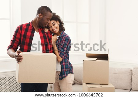 Happy african-american couple embracing at new home among moving boxes, copy space. #1006645702