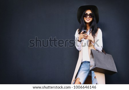 Beautiful Asian well-dressed young irl holding a  brown blank paper bag and makes purchases in an online store against a black wall background with copy space for text or design. Horizontal mockup #1006646146