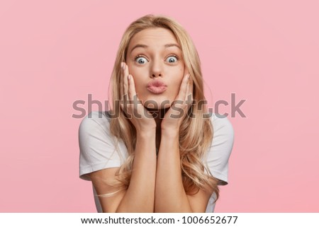 Pleased funny woman pouts lips and looks with bugged eyes at camera, makes grimace, has attractive look, isolated over pink background. Indoor shot of beautiful young female poses indoor in studio