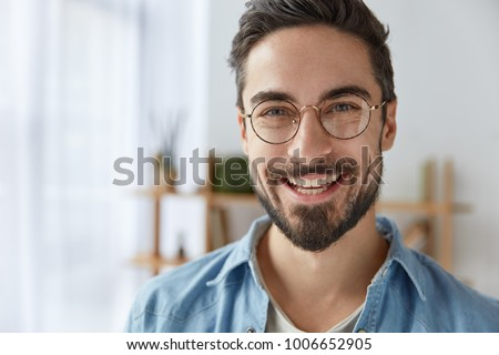 Close up shot of cheerful satisfied attractive male with stubble, has broad smile, wears round spectacles, rejoices success at work, stands against cozy interior. Fashionable designer glad be praised Royalty-Free Stock Photo #1006652905
