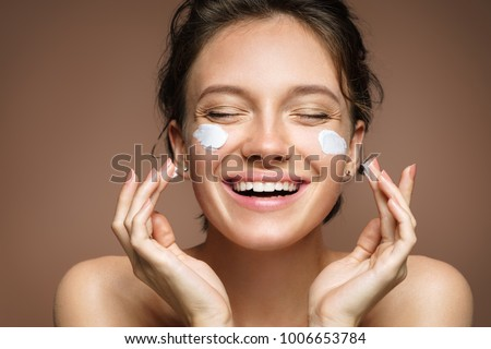 Laughing girl applying moisturizing cream on her face. Photo of young girl with flawless skin on brown background. Skin care and beauty concept #1006653784
