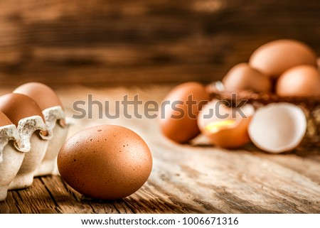 Brown eggs in carton box. Broken egg with yolk in background.  Royalty-Free Stock Photo #1006671316