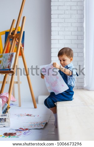 Cute, happy, white boy in blue shirt and jeans sitting with palette in studio and looking to window. Little child among colorful pictures. Concept of early childhood education, happy family, parenting #1006673296