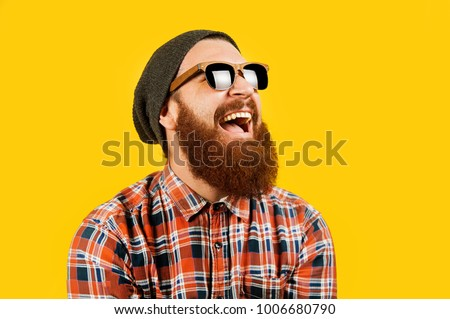 Portrait of young hipster man in sunglasses and hat posing on yellow background. Smiling bearded man wearing sunglasses, studio shot. Happy man with beard looking up. #1006680790