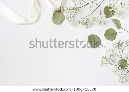 Styled stock photo. Feminine wedding desktop mockup with baby's breath Gypsophila flowers, dry green eucalyptus leaves, satin ribbon and white background. Empty space. Top view. Picture for blog. Royalty-Free Stock Photo #1006715578