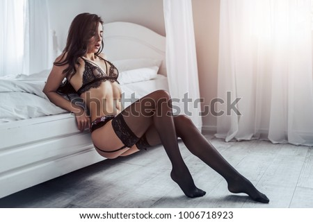 Sexy young woman in black lace lingerie and stockings is sitting on white bed.