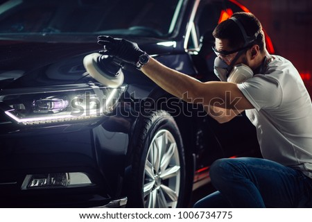 Car detailing - Hands with orbital polisher in auto repair shop. Selective focus. Royalty-Free Stock Photo #1006734775