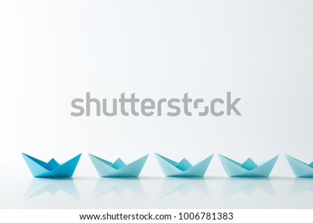 Leadership concept with a dark blue paper ship leading among light blue ships in a row #1006781383