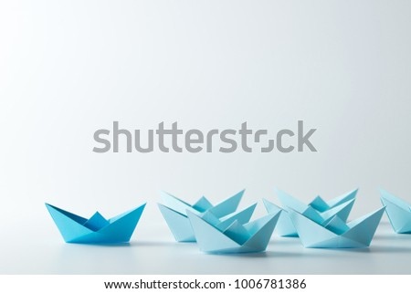 Leadership concept with a dark blue paper ship leading among light blue ships #1006781386