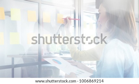 Blurred image, young business woman meeting and use paper notes on glass wall background to share idea, teamwork and brainstorm concept  #1006869214