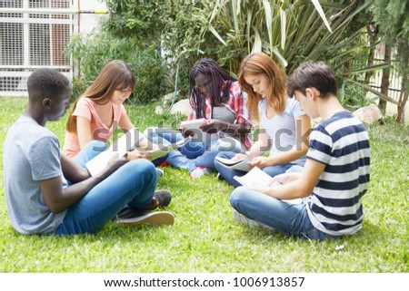 Multi ethnic teenagers friends making school tests outdoor, seated on a park. #1006913857