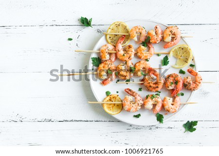 Grilled shrimp skewers. Seafood, shelfish. Shrimps Prawns skewers with spices and fresh herbs on white wooden background, copy space. Shrimps prawns brochette kebab. Barbecue srimps prawns. #1006921765