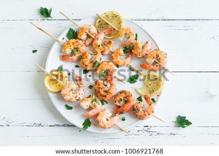 Grilled shrimp skewers. Seafood, shelfish. Shrimps Prawns skewers with spices and fresh herbs on white wooden background, copy space. Shrimps prawns brochette kebab. Barbecue srimps prawns. #1006921768