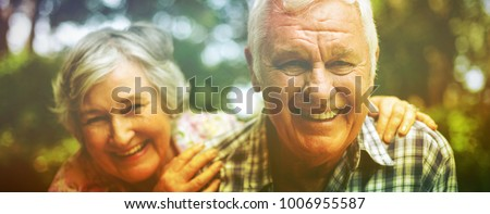 Portrait of senior couple laughing against trees in back yard #1006955587
