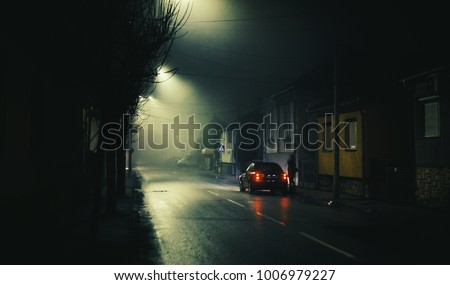 Night scene on foggy street of a small town, lonely woman and one car.  #1006979227