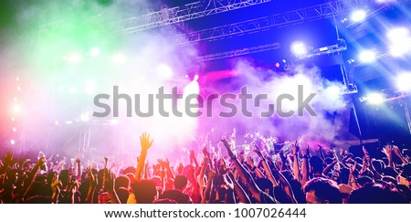 Young people dancing and having fun in summer festival party outdoor - Crowd with hands up celebrating concert event - Soft focus on center hand with yellow background flare - Fun and youth concept #1007026444
