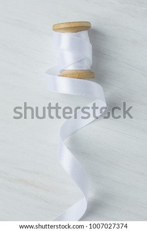 Single Wooden Spool Roll with Curly Silk Ribbon on White Wood Background. Sewing Crafts Hobby Concept. Elegant Styled Stock Image for Social Media Blog Website Workshop Announcement. Copy Space