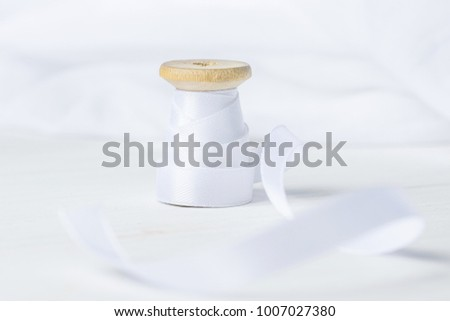 Single Wooden Spool Roll with Silk Ribbon on White Cotton Linen Fabric Background. Sewing Crafts Hobby Concept. Elegant Styled Stock Image for Social Media Blog Website Announcement. Copy Space