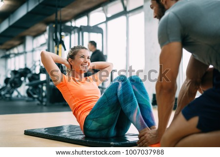 Personal trainer assisting woman lose weight Royalty-Free Stock Photo #1007037988
