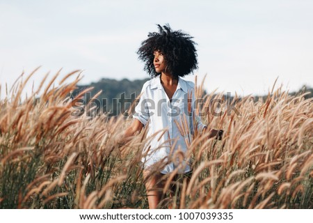 cheerful african american young woman on the field at sunset Royalty-Free Stock Photo #1007039335