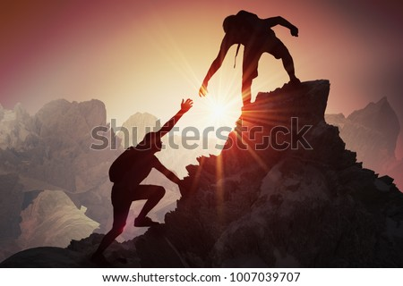 Help and assistance concept. Silhouettes of two people climbing on mountain and helping. Royalty-Free Stock Photo #1007039707