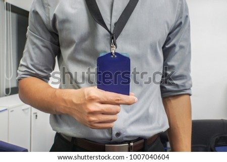 close up businessman with grey shirt hold neck company badge in office #1007040604