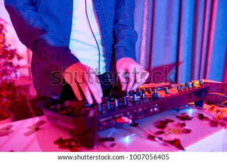 Close up of Djs hands playing music on mixing console during party in nightclub, copy space #1007056405