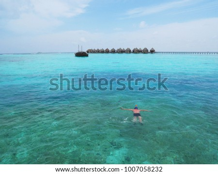 Man swimming in Maldives blue sea water near a tropical resort and traditional Maldivian boat in the background. Maldives' atolls are one of the best places on earth for scuba and snorkel diving #1007058232
