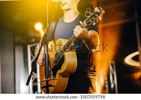 The singer plays an acoustic guitar and sings at a concert Royalty-Free Stock Photo #1007059798